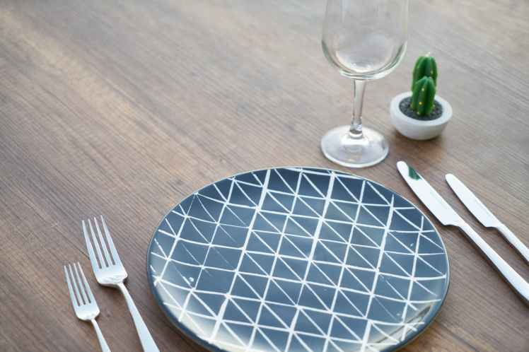 round blue and white ceramic plate two forks two knives and wine glass